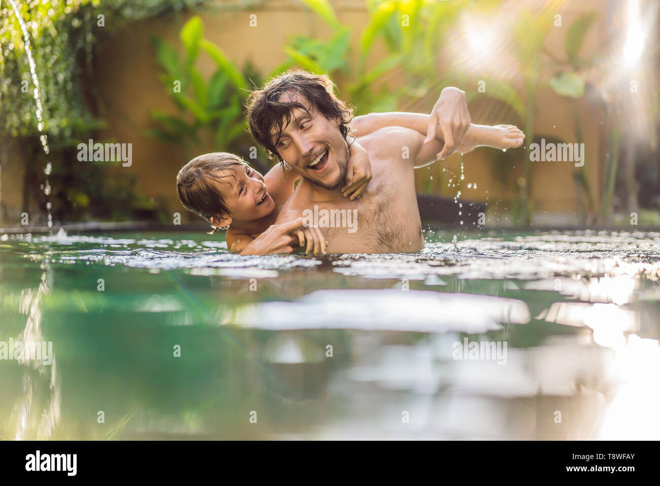 Padre e hijo se divierten en la piscina Foto de stock
