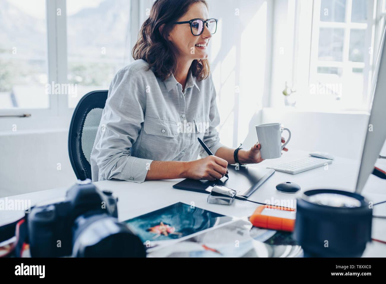 Mujer joven sentado en la mesa de edición de imágenes en el equipo. Fotógrafo retoque fotos femenino en Office mediante tableta gráfica y un lápiz digital. Foto de stock