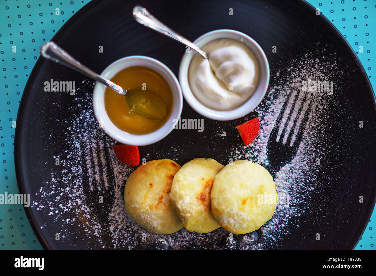 Desayuno saludable cottage cheesecakes Federación sirniki con miel y crema agria para desayunar sobre fondo azul. Foto de stock