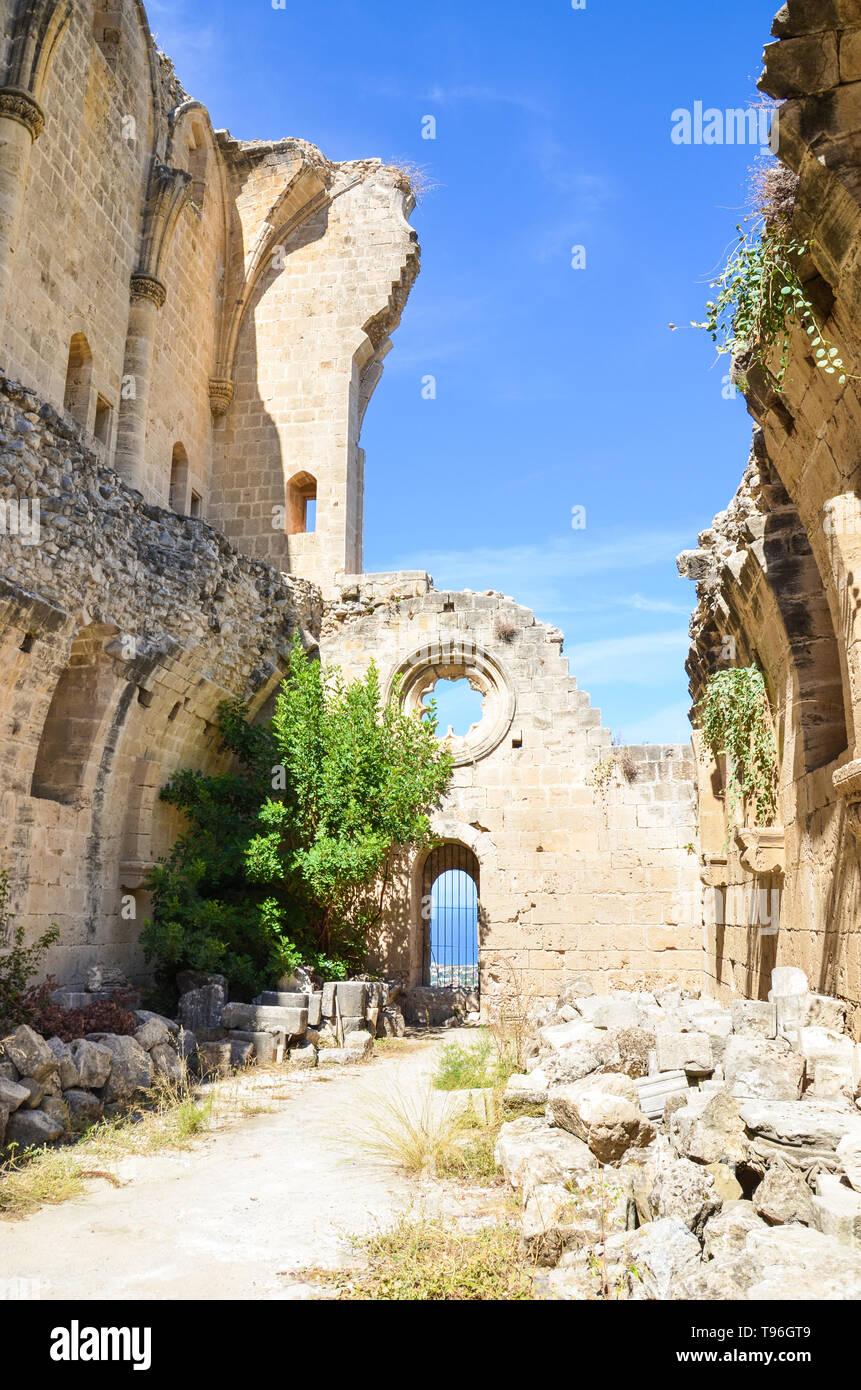 Las ruinas de los muros de la hermosa Abadía de Bellapais en Bellapais, Chipre Septentrional. El histórico monasterio en la parte turca de la isla capturados con el cielo azul en una imagen vertical. Atracción popular. Foto de stock