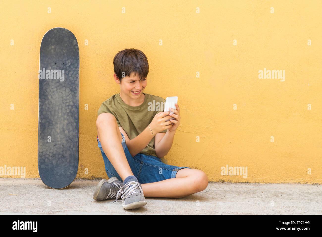 c20be8ee08 Vista frontal de la joven sentada en el suelo apoyándose sobre una pared  amarilla mientras se
