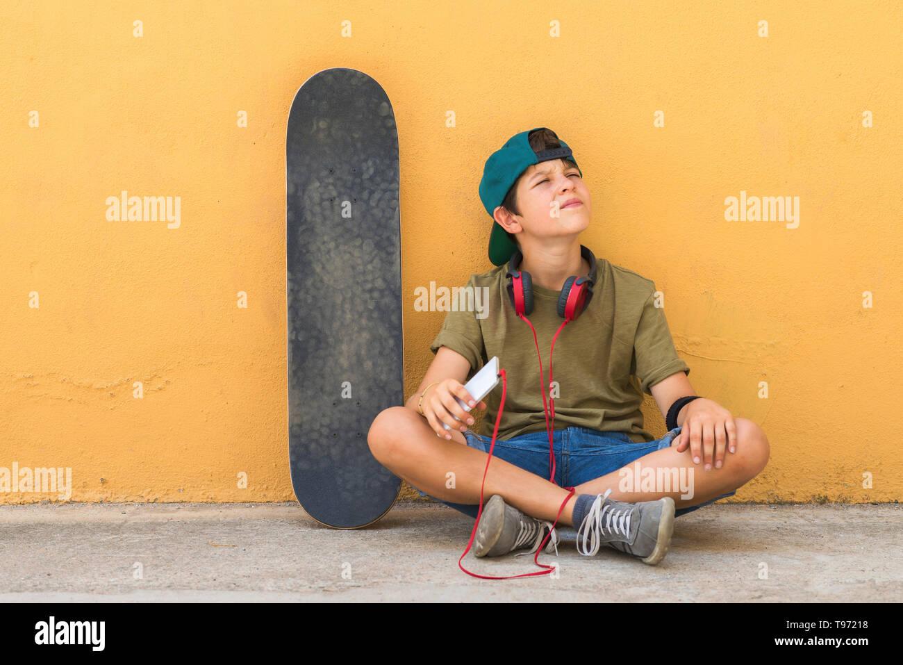 5c685fcd1b Vista frontal de un joven sentado en el suelo apoyándose sobre una pared  amarilla mientras se