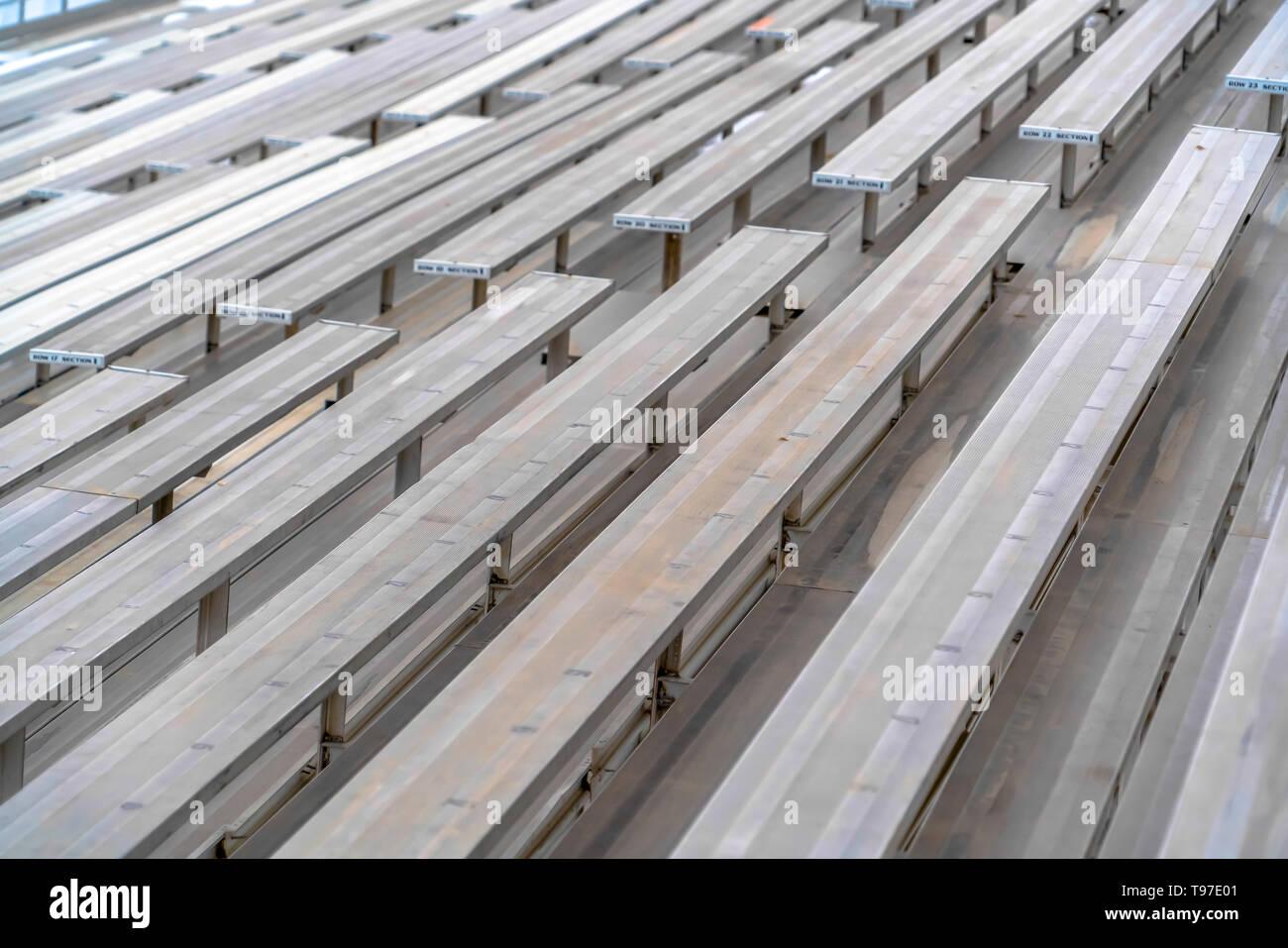 Cerca de tiered filas de bancos en un campo de deportes ver en un día soleado. Imagen De Stock