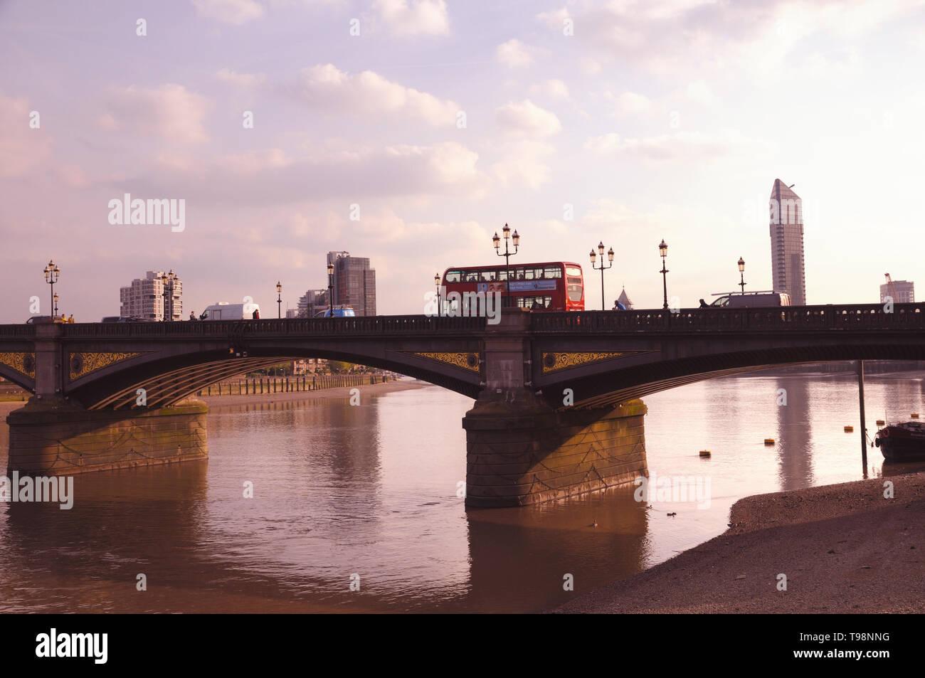 Un autobús de dos pisos rojo en Battersea puente que cruza el río Támesis, Chelsea Embankment, Londres, Inglaterra, Reino Unido. Foto de stock
