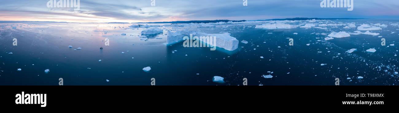Los icebergs y velero en la bahía Disko del solsticio, Groenlandia Foto de stock
