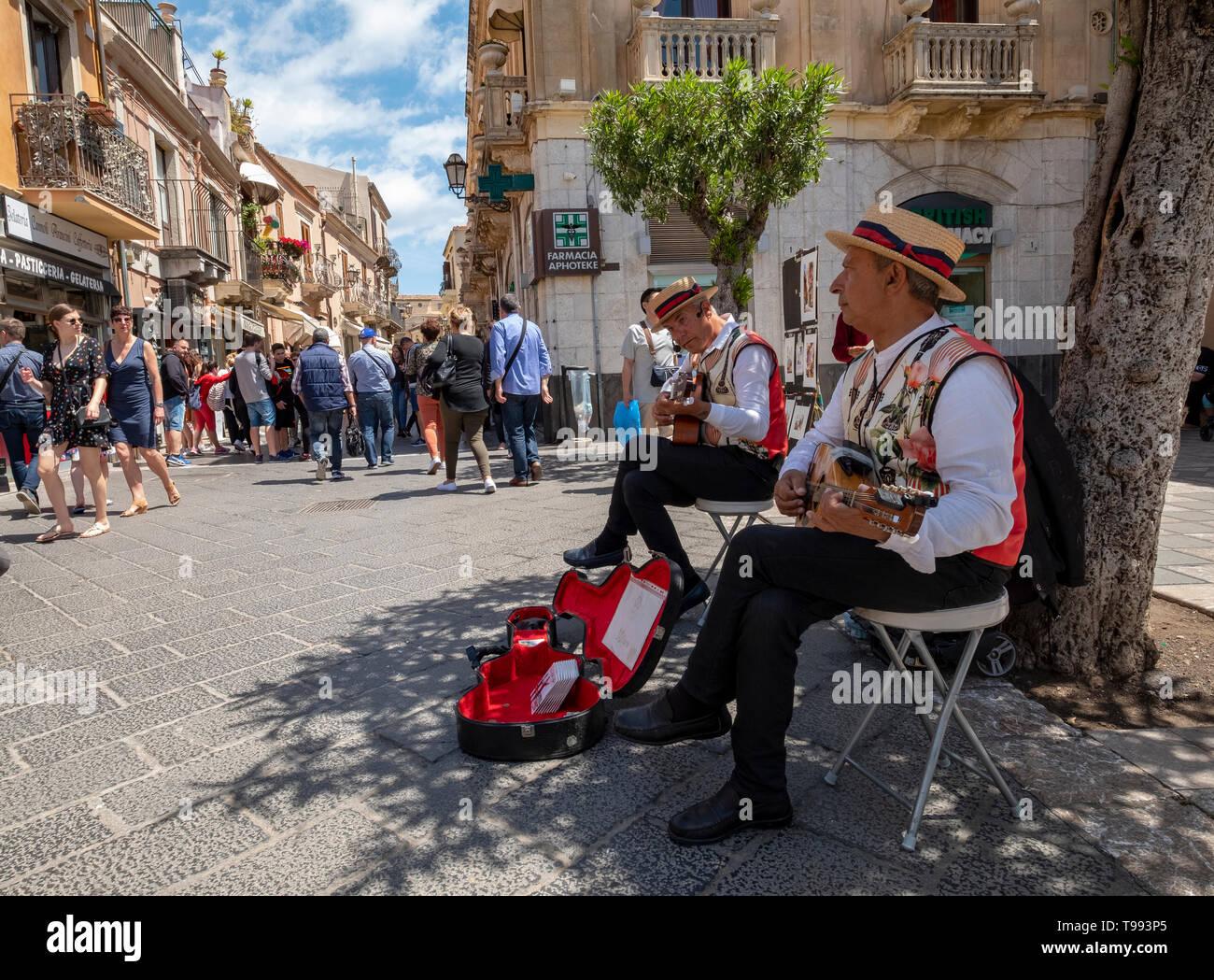 Los músicos callejeros juegan en el Corsa Umberto, Taormina, Sicilia. Imagen De Stock