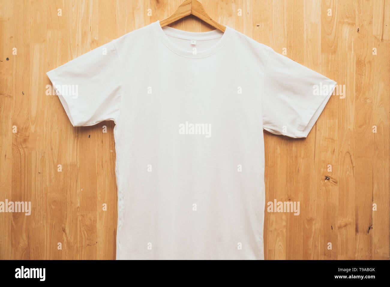Blanco camiseta de manga corta con cuello redondo liso maqueta concepto back ground de madera vista frontal Imagen De Stock