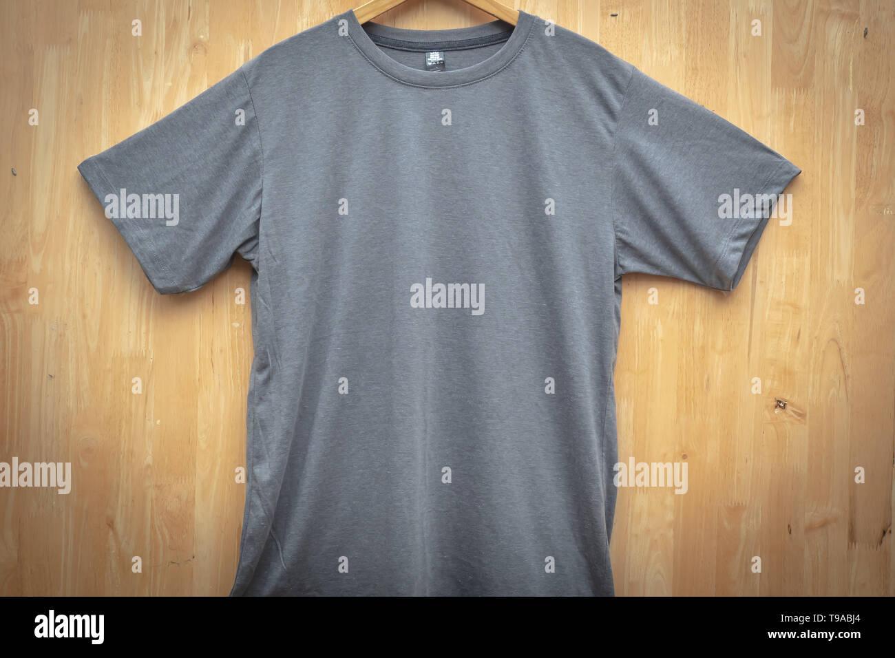 Gris camiseta de manga corta con cuello redondo liso maqueta concepto back ground de madera vista frontal Imagen De Stock