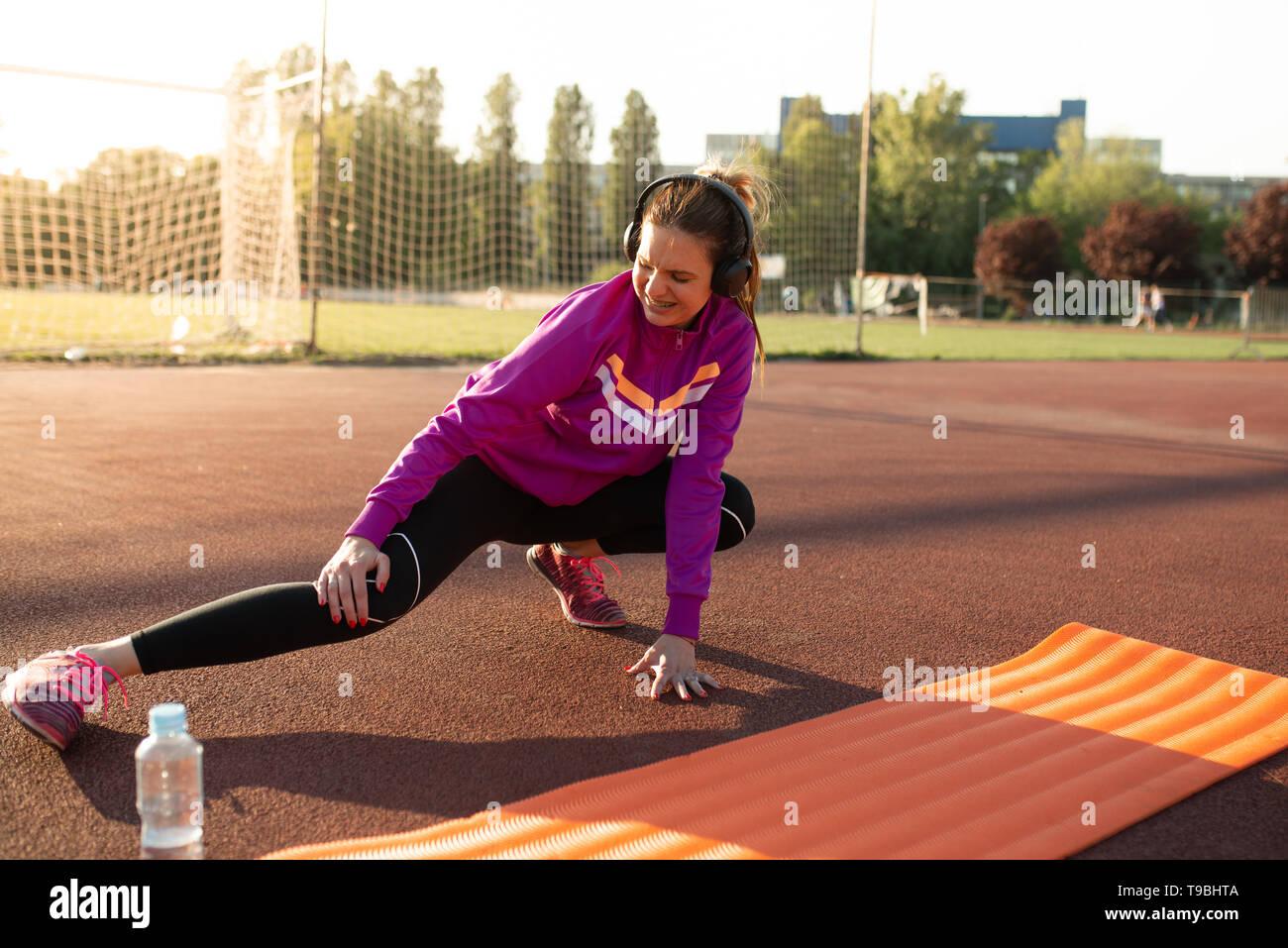 Joven mujer deportiva herido durante ejercicios de MAT en un día soleado Imagen De Stock