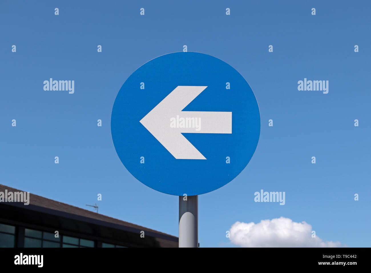 """Blanco reflectante en brillante azul reflectante """"Keep Left"""" signo contra un cielo azul claro Foto de stock"""