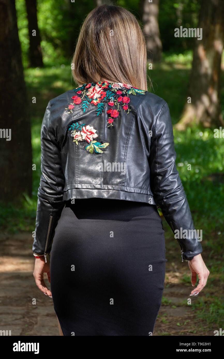 f8072838753bf9 Mujer joven con una chaqueta de cuero negro con motivos florales decoración  artesanal en el bosque