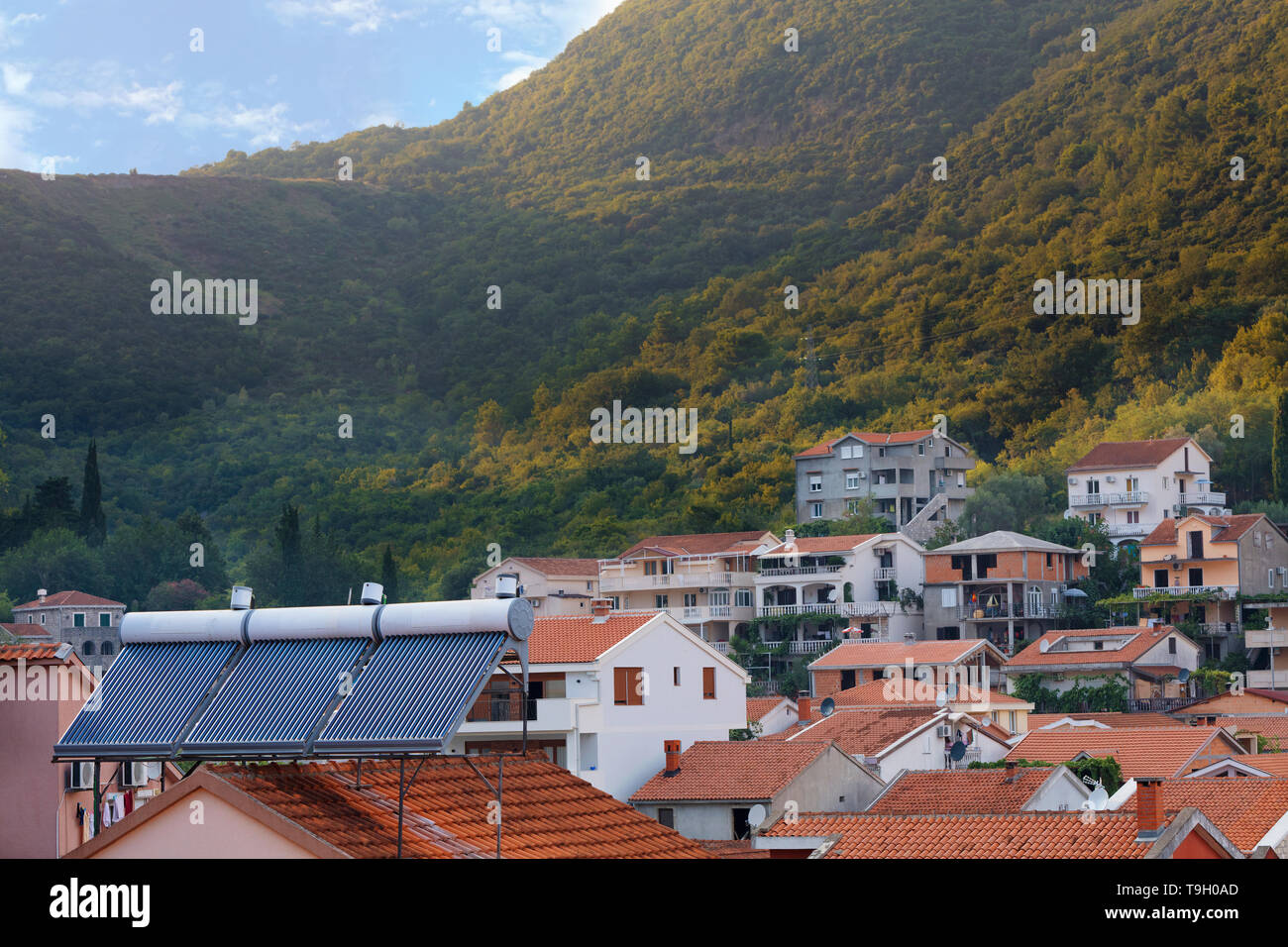 Calentadores solares de agua renovable moderna están instalados en el techo de tejas de naranja de la casa con el telón de fondo de un paisaje de montaña de Montenegro Imagen De Stock