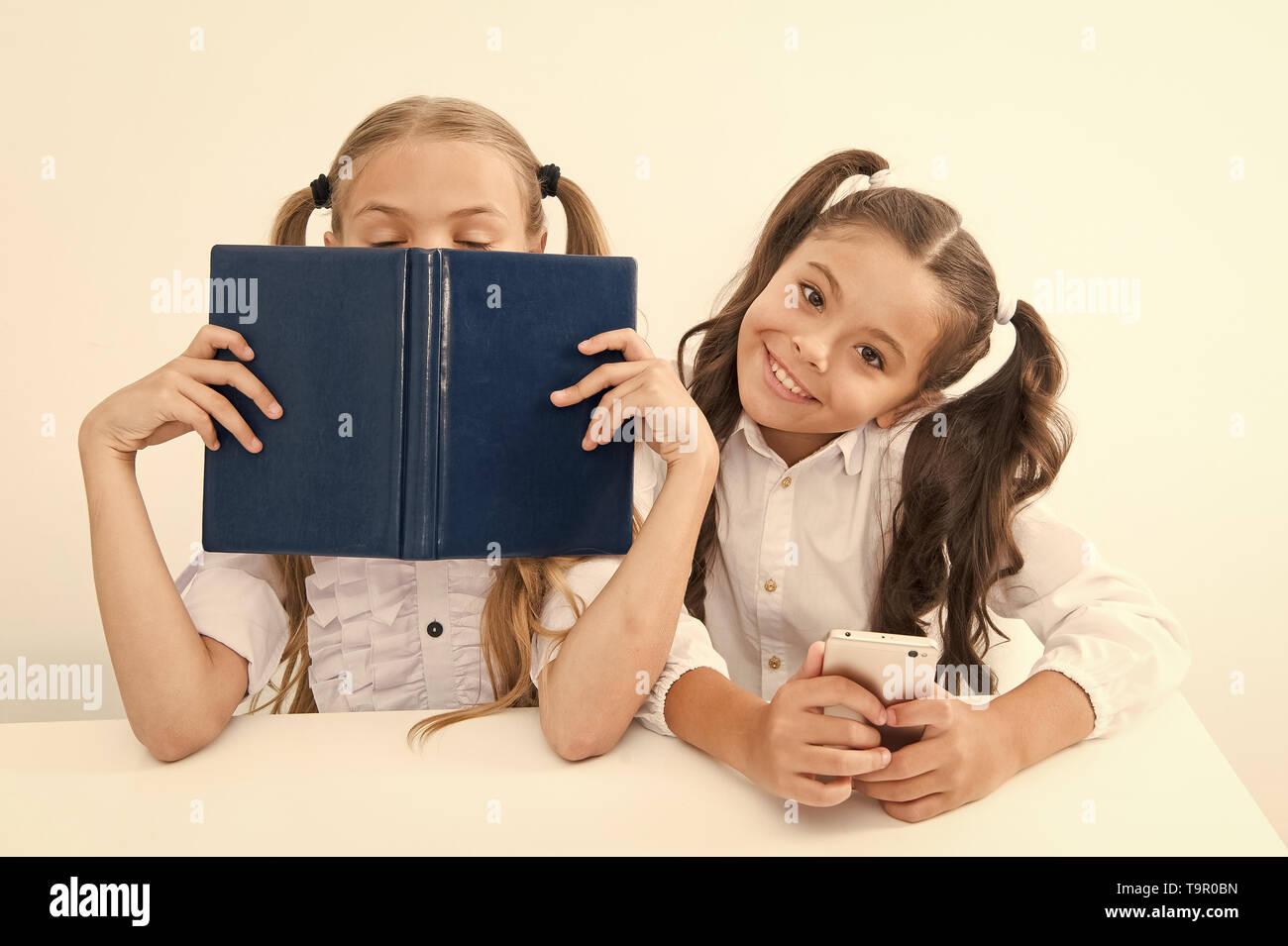 Contra la vieja escuela moderna. Colegiala mantenga teléfono móvil smartphone moderno mientras su amiga disfrute de libro viejo como almacenamiento de datos analógicos. Tecnología contra e Foto de stock