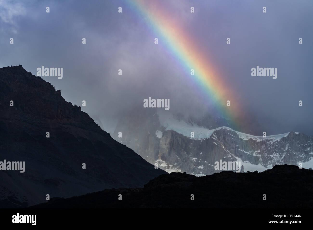 Un arco iris en las nubes enshrouding Monte Fitz Roy en el Parque Nacional Los Glaciares, cerca de El Chaltén, Argentina. Un sitio de Patrimonio Mundial de la UNESCO en el PAT Foto de stock