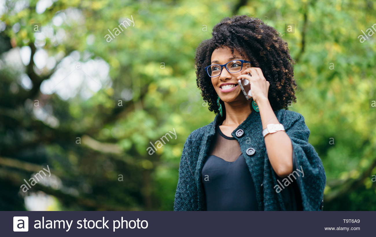 Los jóvenes negros expresivos sorprendente mujer recibiendo noticias de teléfono celular en el exterior del parque en temporada de otoño. Moda chica con el cabello afro. Imagen De Stock