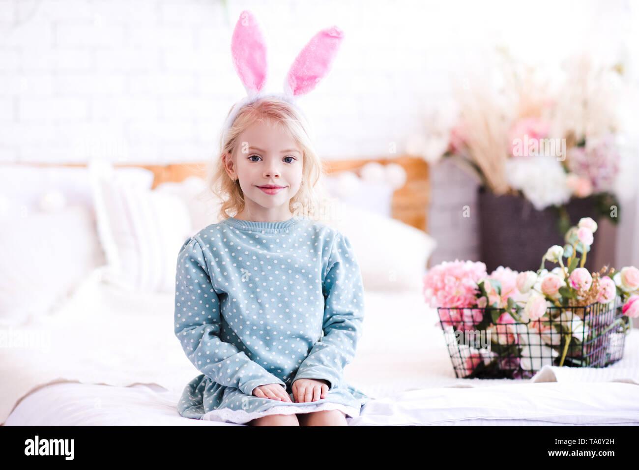 Lindo bebé niña 4-5 años vistiendo elegante vestido y orejas de conejo con diadema de flores en el fondo. Mirando a la cámara. El tiempo de primavera. Foto de stock