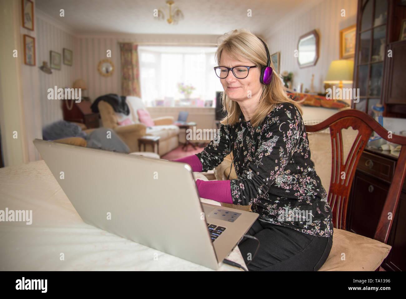 Una madre que trabaja en casa,online con su ordenador mirando su pantalla con interés. Foto de stock