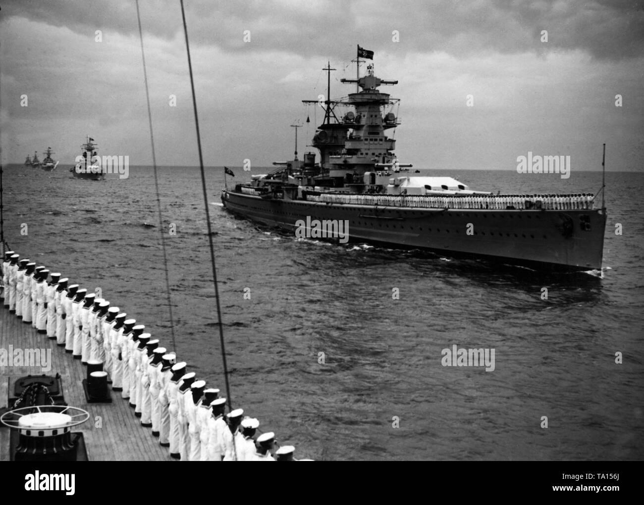 """Revisión de la flota cerca de Kiel con ocasión del 20º aniversario de la batalla en el mar Skagerrak (Batalla de Jutlandia). El aviso de """"rejilla"""", estado de Hitler de yates, se acaba de pasar por el heavy cruiser / Buque acorazado 'Admiral Graf Spee'. Los marineros en la rejilla """"stand"""" en el desfile de la formación. Foto de stock"""