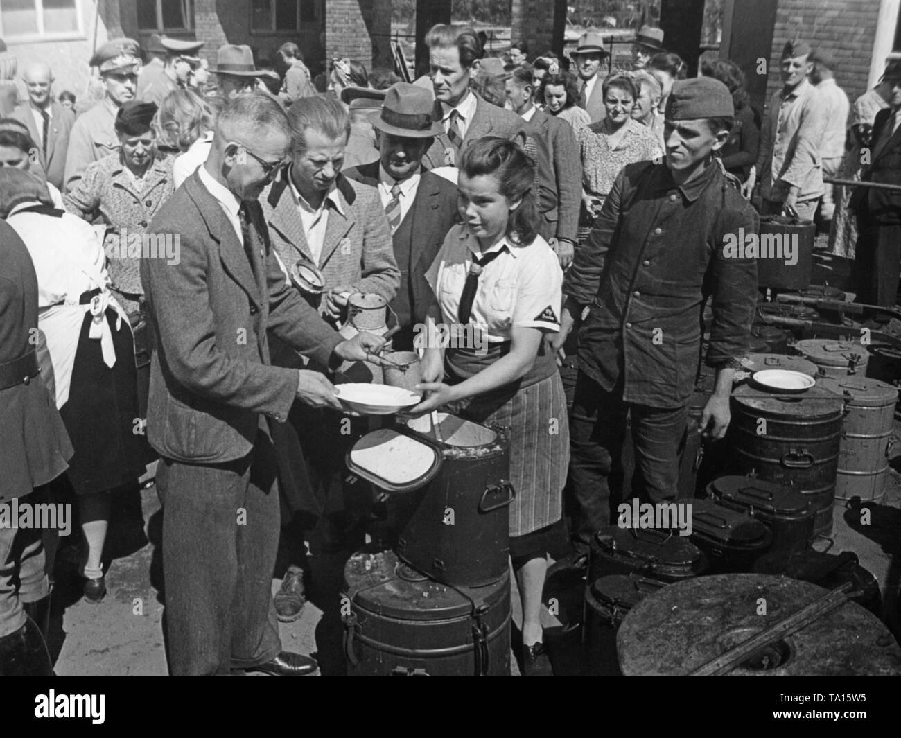 El BDM distribuye alimentos calientes para bombardear a las víctimas en un centro de atención en Berlín. Foto de stock