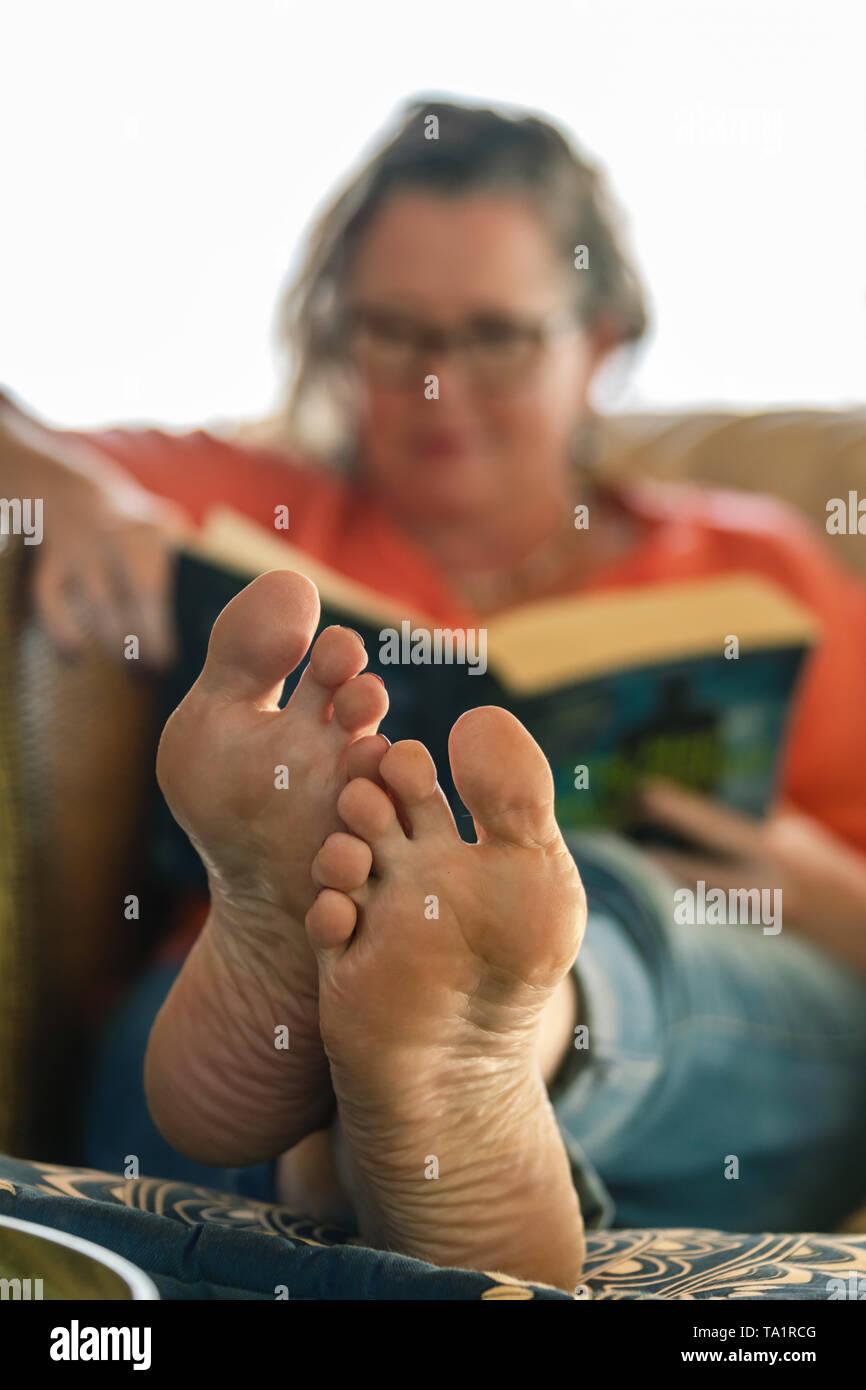 Mujer de mediana edad leer y relajarse en el sofá Imagen De Stock