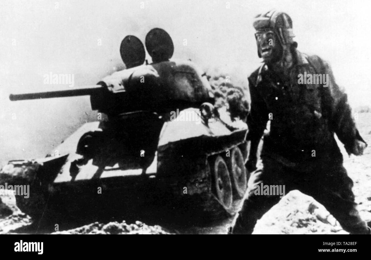 En este innegable ruso impresionante foto tomada durante la Batalla de Berlín, el comandante de tanques ruso ha sido capaz de hacer una salida de último minuto desde su tanque que ha sido golpeado y prendieron fuego. Salvaje con emoción, el comandante está gritándole a sus camaradas, ordenándoles a continuar su ataque. Imagen De Stock