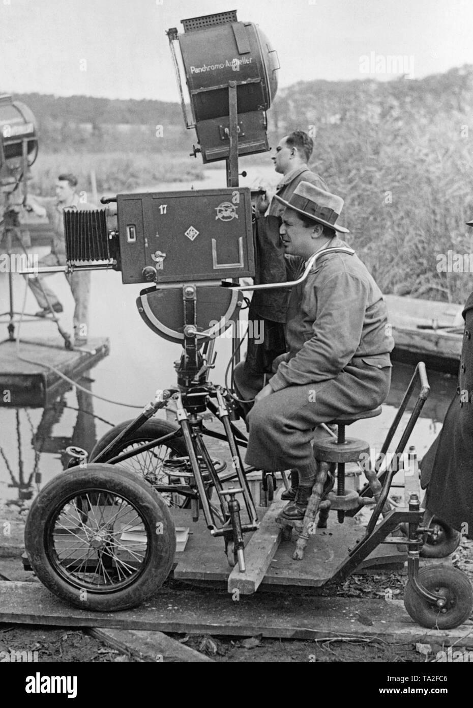 """Foto de un camarógrafo el rodaje de la película """"El Barón gitano', dirigida por Karl Hartl. El camarógrafo se asienta sobre un vehículo de cuatro ruedas circule sobre rieles. La cámara en sí es también montado en este vehículo por medio de un trípode, por lo que ambos son móviles. Foto de stock"""