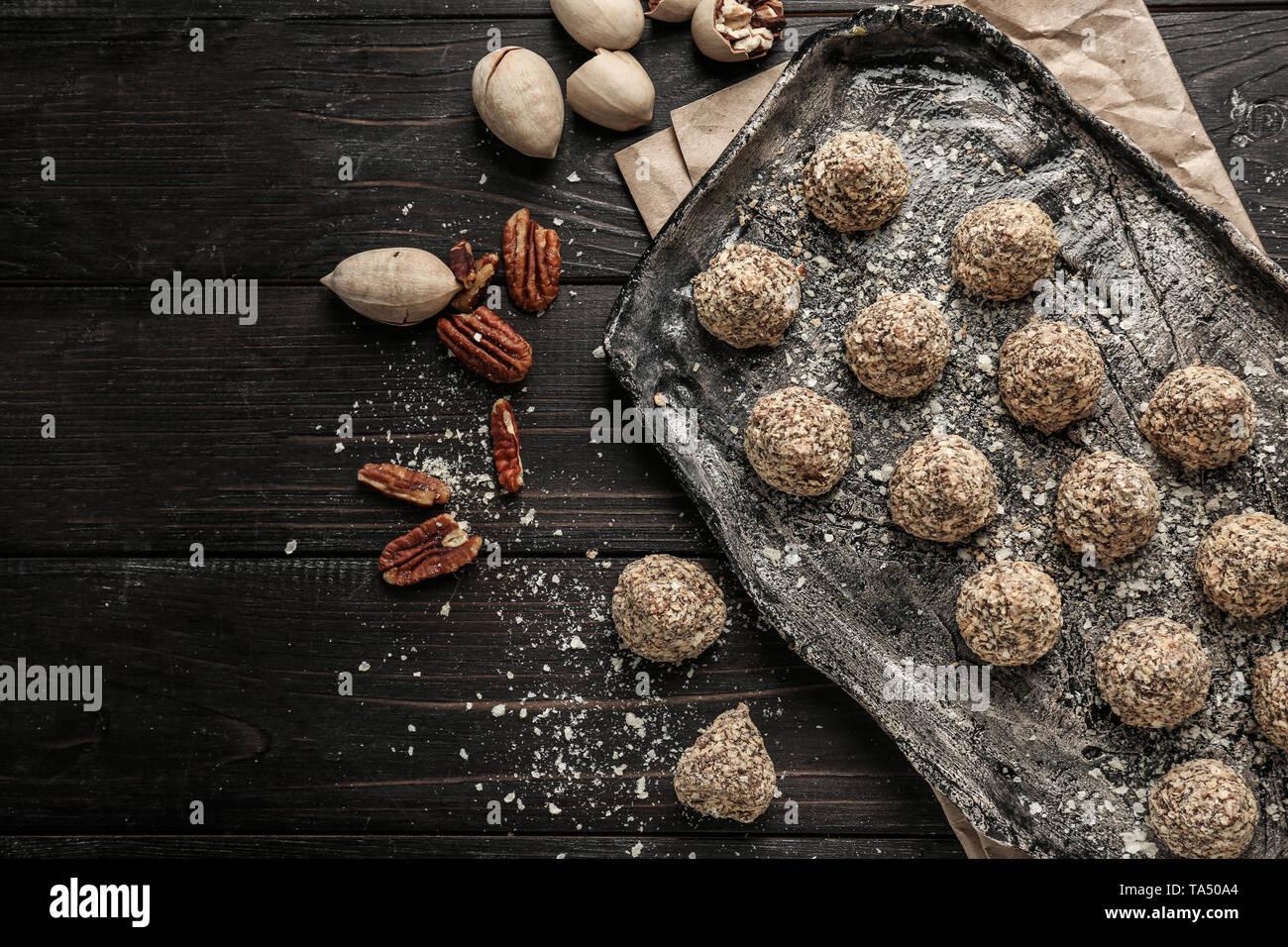 Placa con sabrosos dulces trufas en mesa de madera oscura Foto de stock