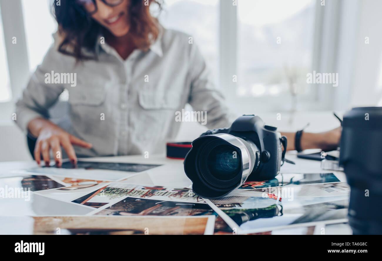 Artista Femenina trabaja en el bloc de dibujo en la oficina mientras se mira la imagen se imprime. Mujer joven retocar imágenes. Foto de stock