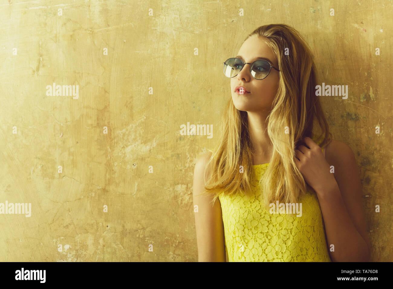 3ce348b8d Chica bonita con largo pelo rubio en vestido amarillo, gafas de sol Imagen  De Stock
