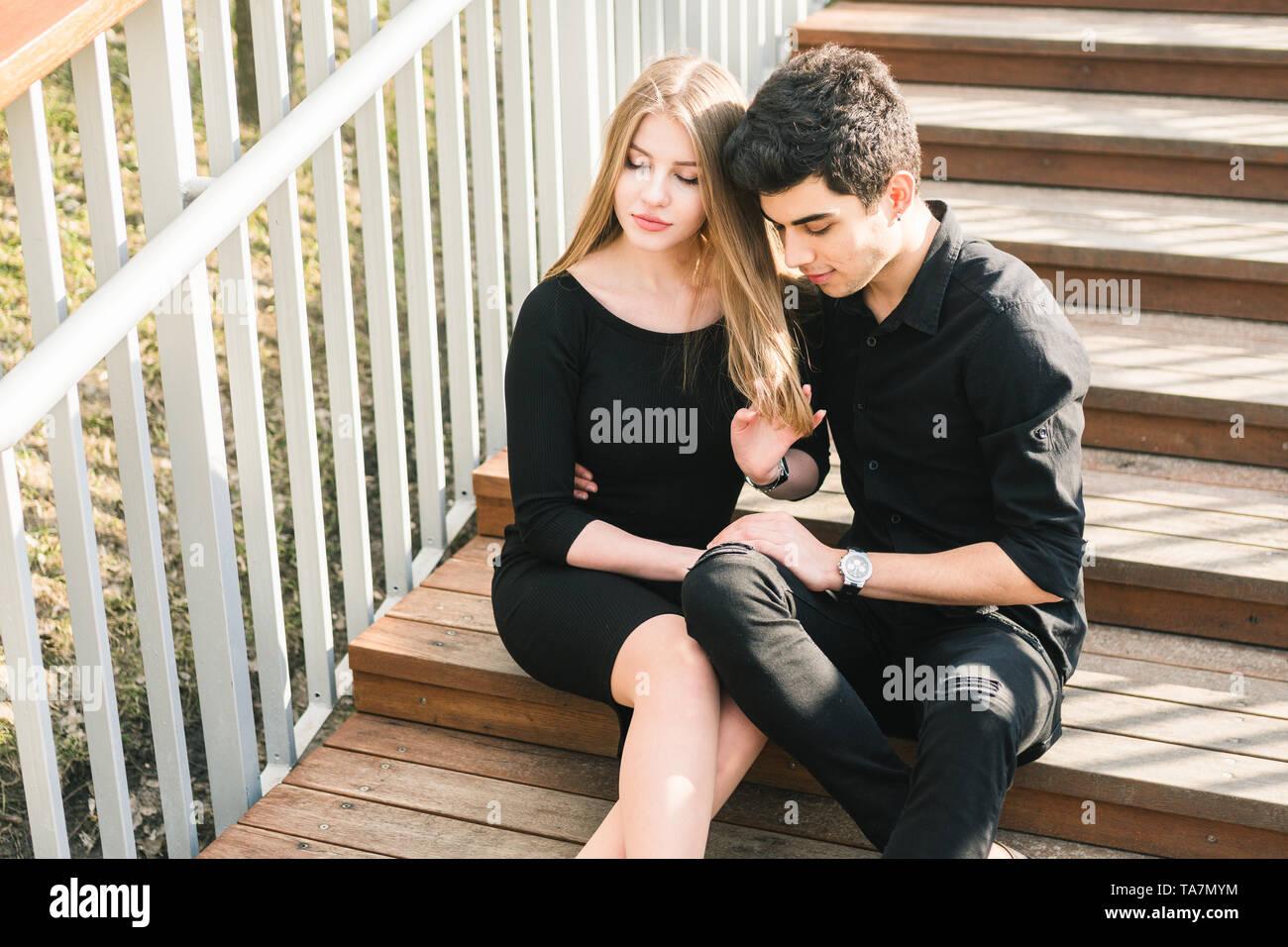 Hermosa joven pareja multirracial, estudiante par en amor, sentarse escalera de madera en la ciudad. Hermosa morena turco guy abrazo caucásico chica en Foto de stock