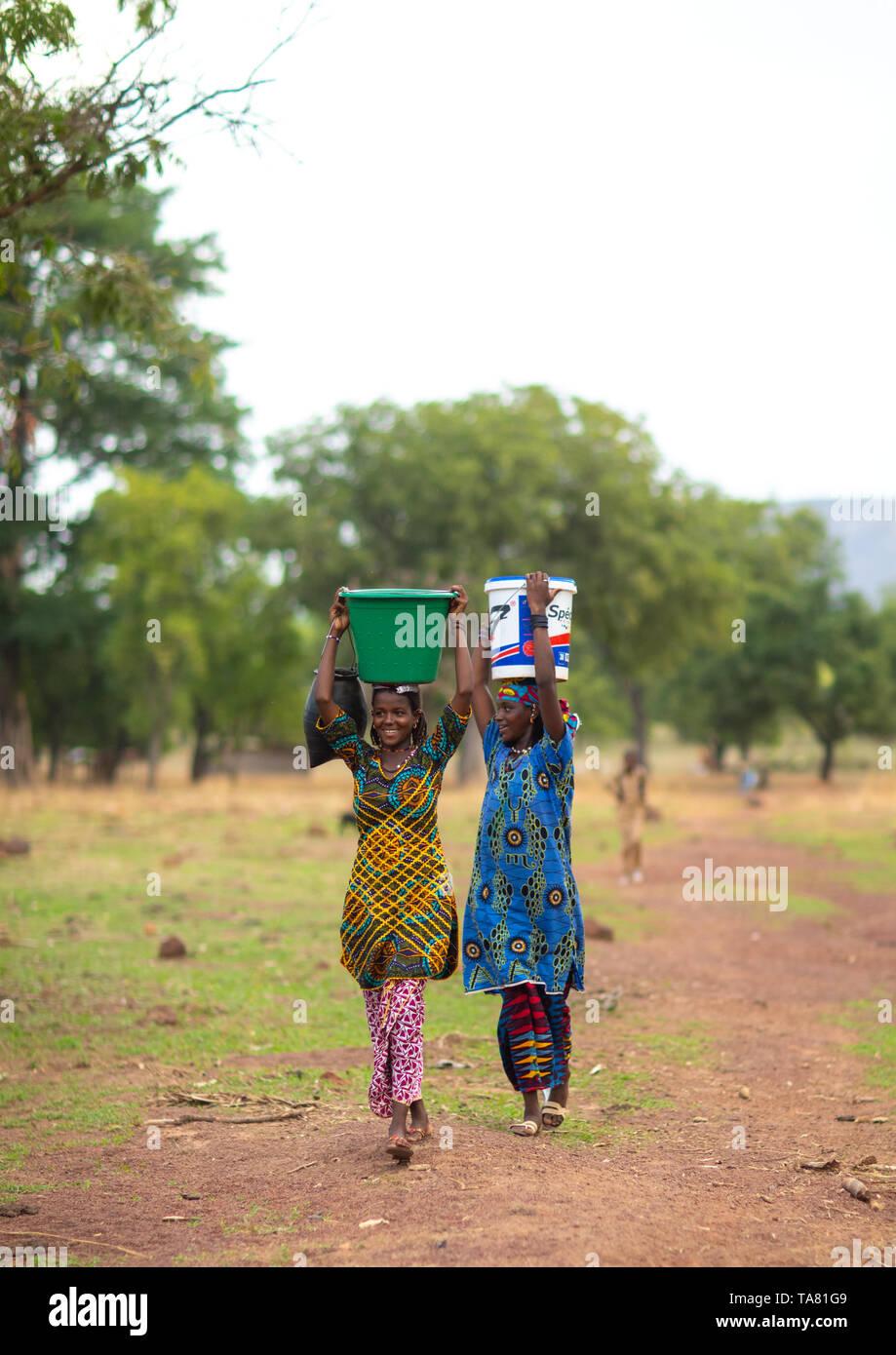 Tribu Peul niñas llevando cubos llenos de agua en la cabeza, distrito Savanes, Boundiali, Costa de Marfil Foto de stock