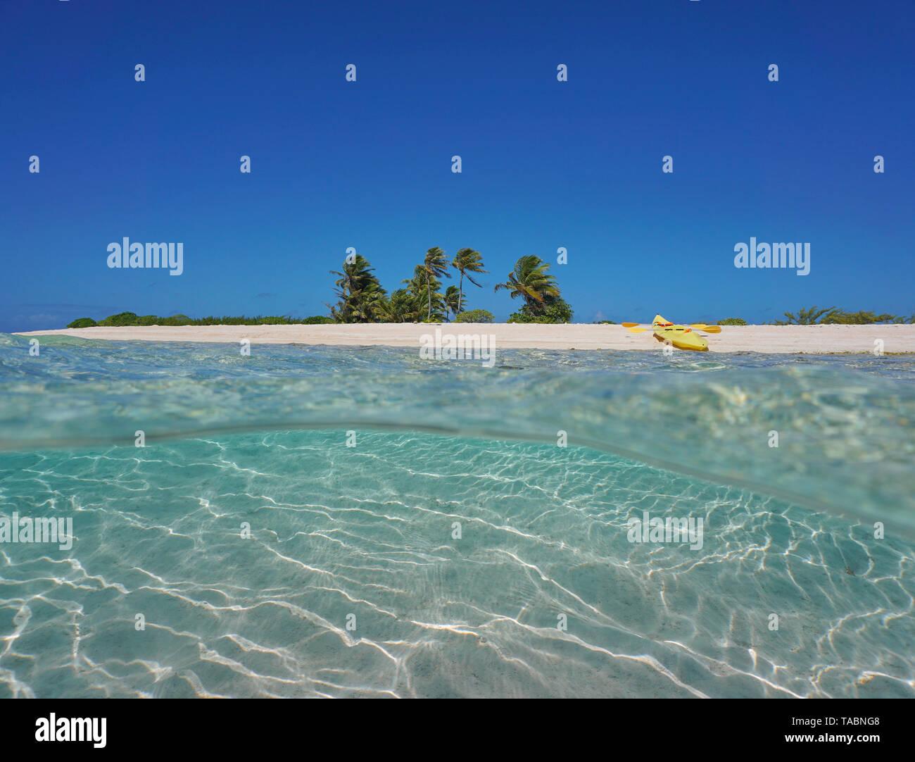 Isla tropical de arena con un kayak de mar en la playa de arena y submarinas, Polinesia francesa, Océano Pacífico, vista dividida por la mitad y bajo el agua. Foto de stock