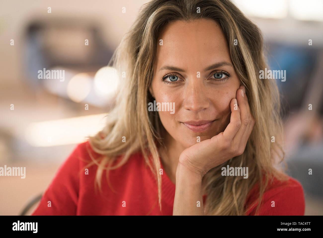 Retrato de mujer rubia sonriente descansar su cabeza en la mano Foto de stock