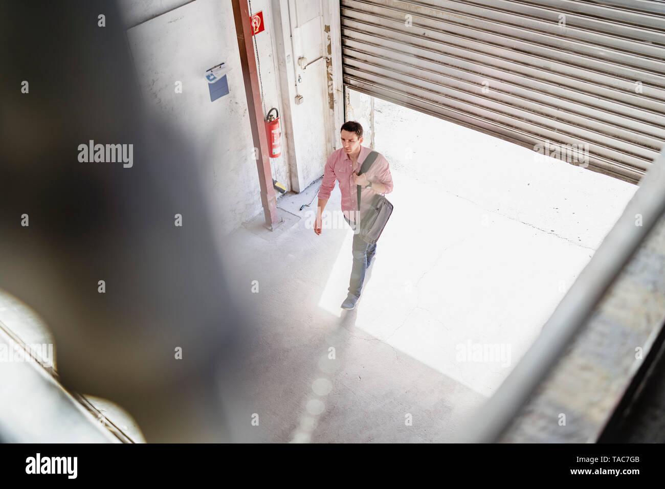 Vista de pájaro del empleado al caminar por la bahía de carga en una fábrica Foto de stock