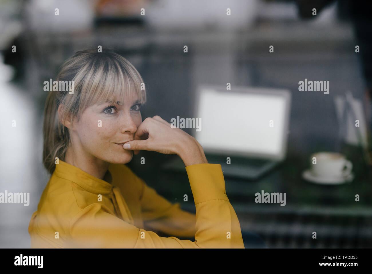 La empresaria rubia sentada a la ventana, pensando Foto de stock
