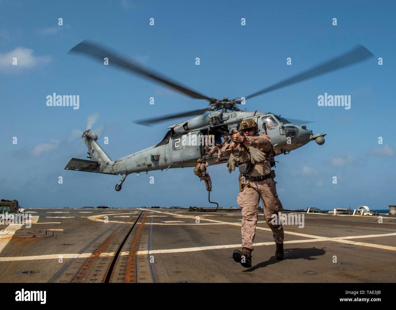 """190518-N-SS350-0113 Mar Arábigo (18 de mayo de 2019), los infantes de Marina asignados a la 22ª Unidad Expedicionaria de los Infantes de Marina (MEU) fast-cuerda de un MH-60 Mar helicóptero Halcón, asignados a los """"cargadores"""" de Mar escuadrón de helicópteros de combate (HSC) 26, en la cubierta de vuelo de la clase Arleigh Burke de misiles guiados destructor USS Bainbridge (DDG 96) durante una visita, junta, búsqueda e incautación de formación. El Abraham Lincoln Carrier Strike Group (ABECSG) y KAARSARGE Amphibious disposición Group (KSGARG) están realizando operaciones conjuntas en los EE.UU. 5ª zona de operaciones de la flota. El KSGARG ABECSG y, con la 22ª MEU, se prepar Imagen De Stock"""