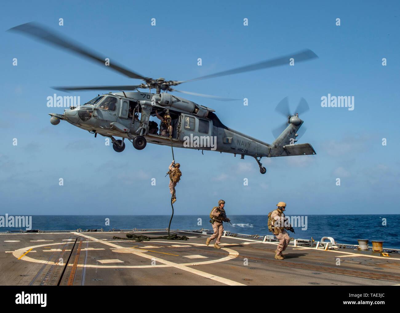 """190518-N-SS350-1054 Mar Arábigo (18 de mayo de 2019), los infantes de Marina asignados a la 22ª Unidad Expedicionaria de los Infantes de Marina (MEU) fast-cuerda de un MH-60 Mar helicóptero Halcón, asignados a los """"cargadores"""" de Mar escuadrón de helicópteros de combate (HSC) 26, en la cubierta de vuelo de la clase Arleigh Burke de misiles guiados destructor USS Bainbridge (DDG 96) durante una visita, junta, búsqueda e incautación de formación. El Abraham Lincoln Carrier Strike Group (ABECSG) y KAARSARGE Amphibious disposición Group (KSGARG) están realizando operaciones conjuntas en los EE.UU. 5ª zona de operaciones de la flota. El KSGARG ABECSG y, con la 22ª MEU, se prepar Imagen De Stock"""