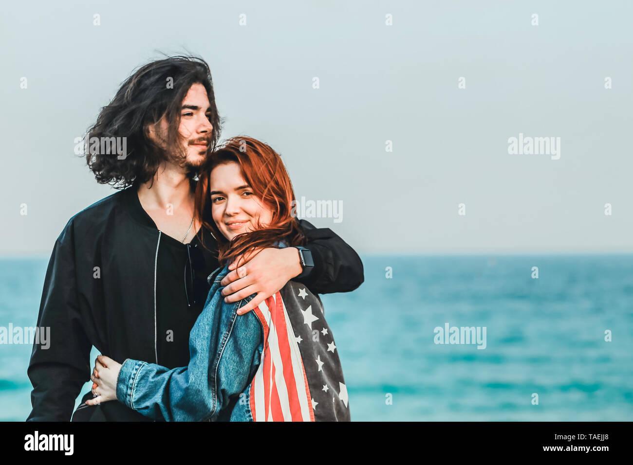 Feliz pareja joven con vista al mar en un cálido día de primavera. Guapo suavemente abraza a su bella pelirroja sweetheart. Foto de stock