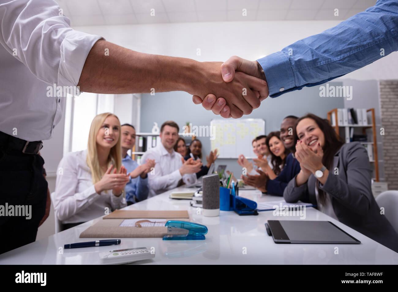 Dos profesionales masculinos un apretón de manos con el equipo por estar Aplaudiendo después de una exitosa reunión Foto de stock