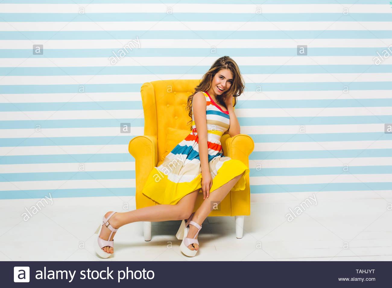 780b6692d Niña morena sonriente en un brillante vestido de verano posando en el  interior, sentado en