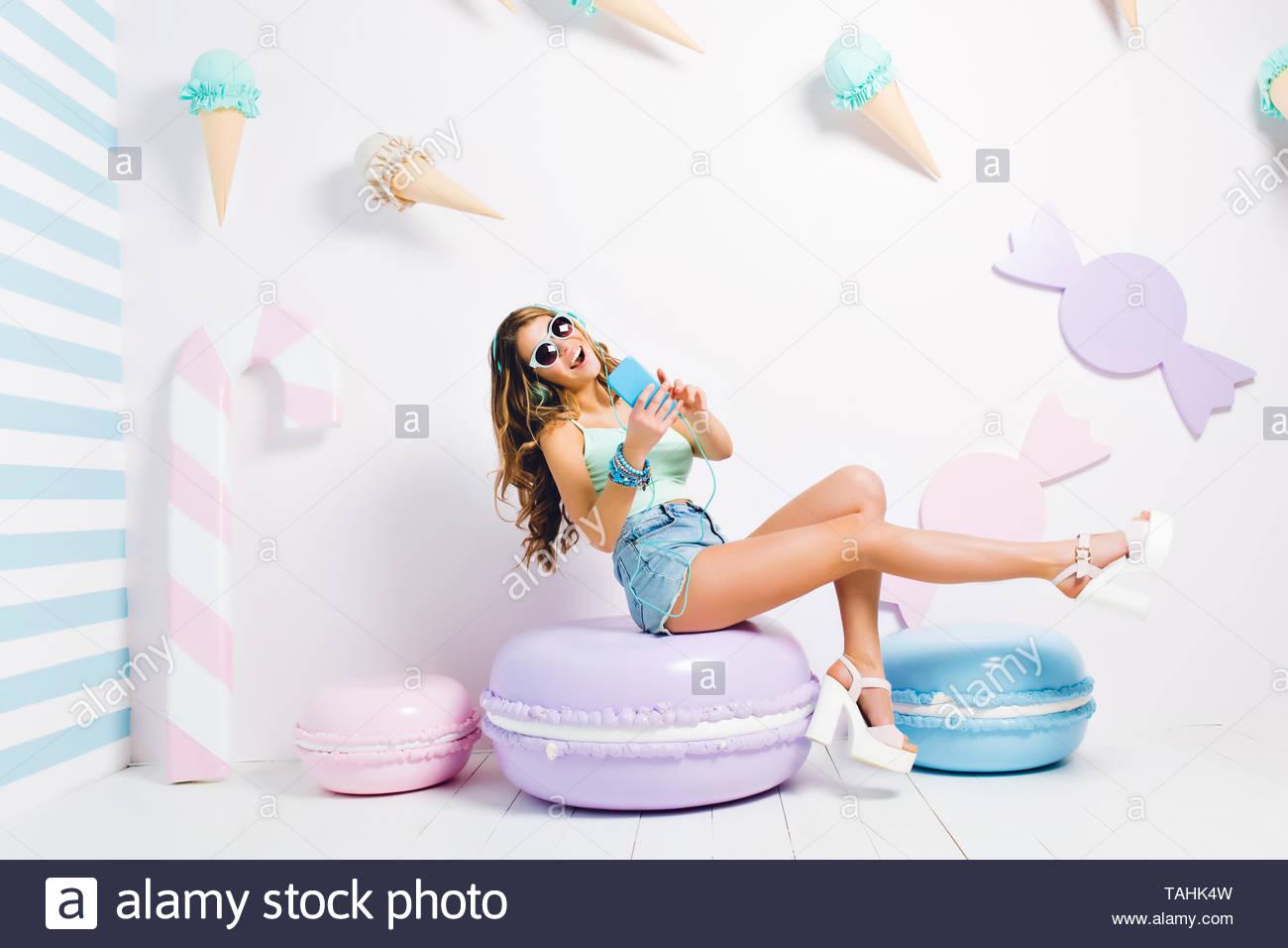 f865224e0fc Graciosa chica con teléfono azul cantando la canción y sonriendo,  descansando en su habitación decorada