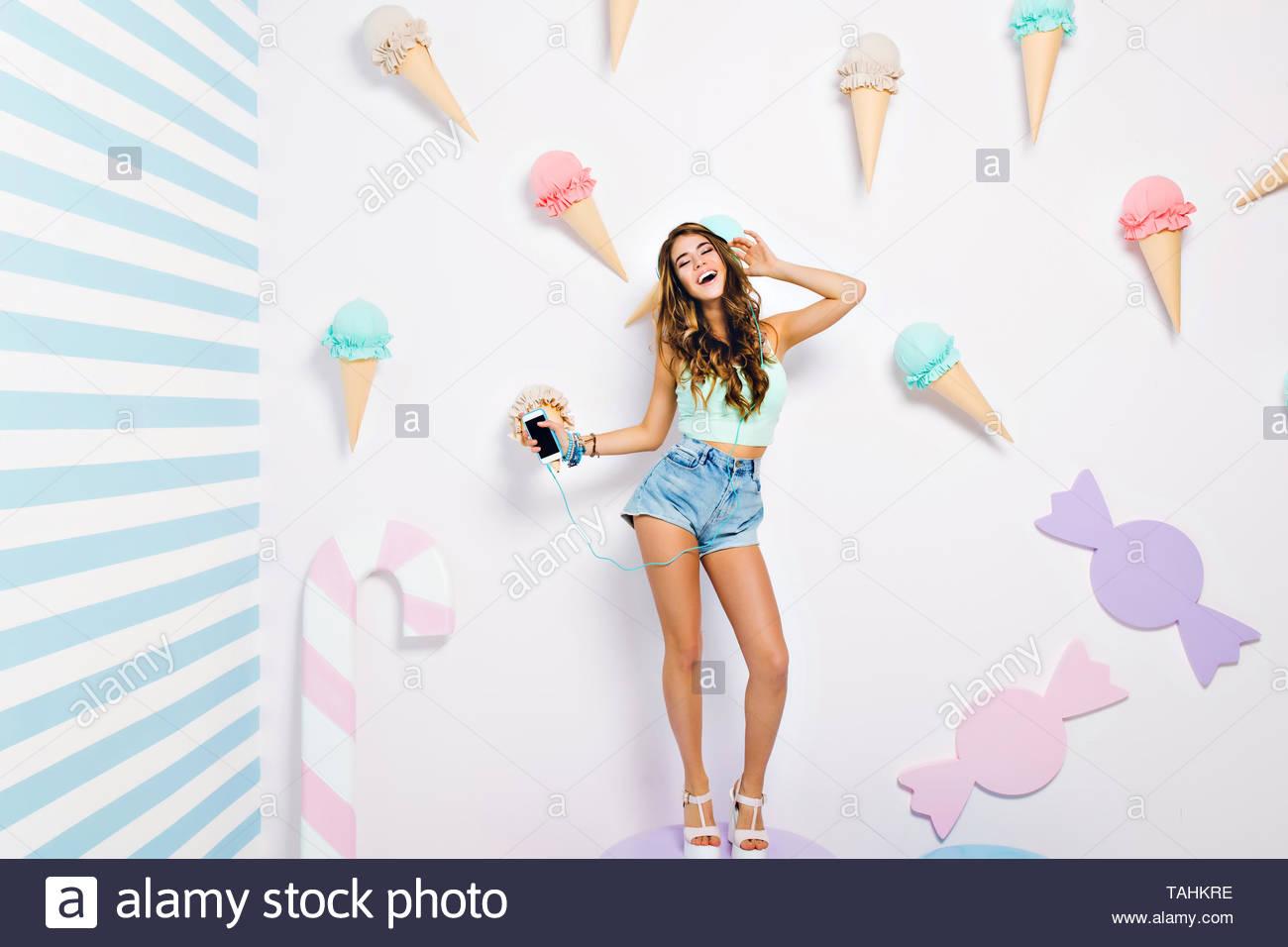 7d53d8aafa6 Ecstatic bronceada chica en denim shorts y sandalias blanco cantando  mientras disfruta de la música en