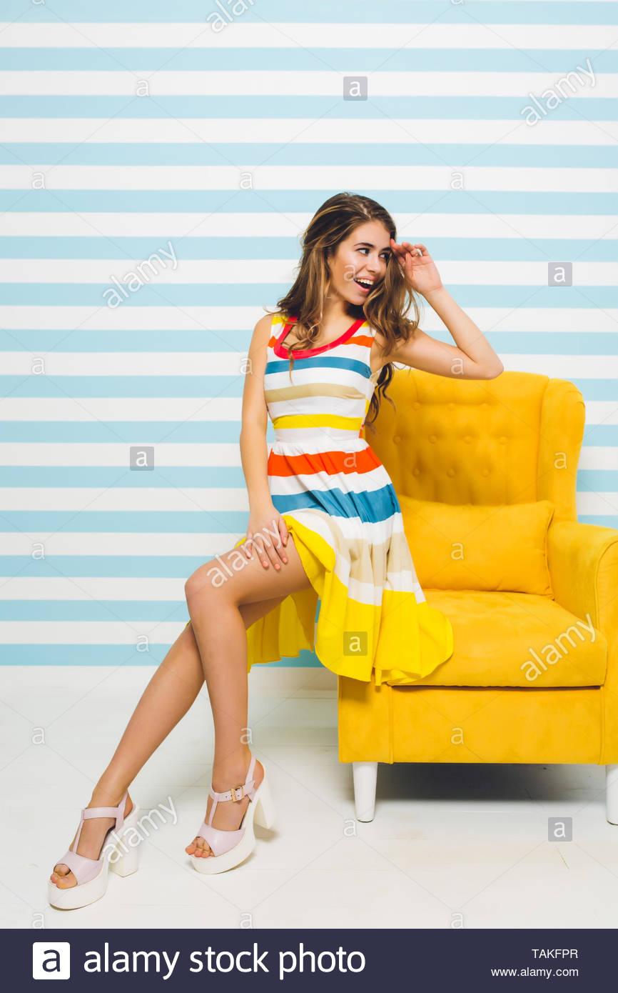 ebb0945a2 Emocionada chica con hermoso peinado mirar lejos, sentado en el mobiliario  moderno de color amarillo
