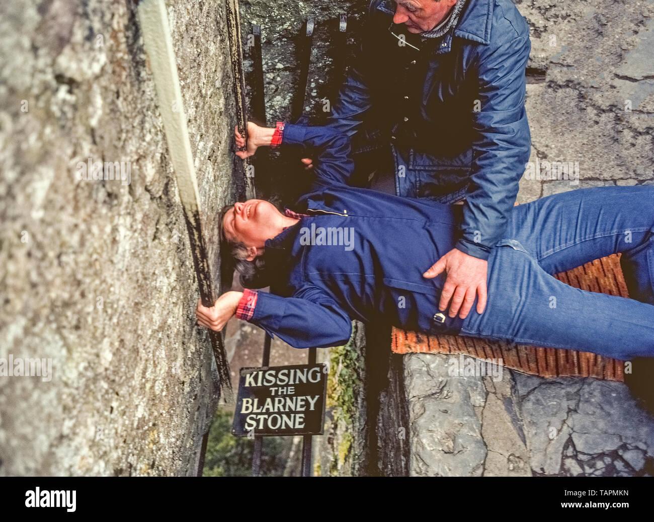 Una operadora se aferra a un joven hombre americano que descansa sobre su espalda, agarra dos pasamanos metálicos, y se inclina la cabeza hacia atrás en la tradicional forma invertida para besar la famosa Piedra de Blarney en lo alto de la torre del Castillo de Blarney en el condado de Cork, Irlanda. Durante mucho tiempo ha sido una tradición para los visitantes del castillo del siglo 15 para subir las estrechas escaleras para llegar al famoso bloque de piedra caliza sobre las almenas que salen de la torre. Barras de hierro que impiden la Les beaux gosses caiga a través del espacio abierto al suelo. Se dice que besar la piedra otorga elocuencia; en otras palabras, darle el don de GAB. Imagen De Stock