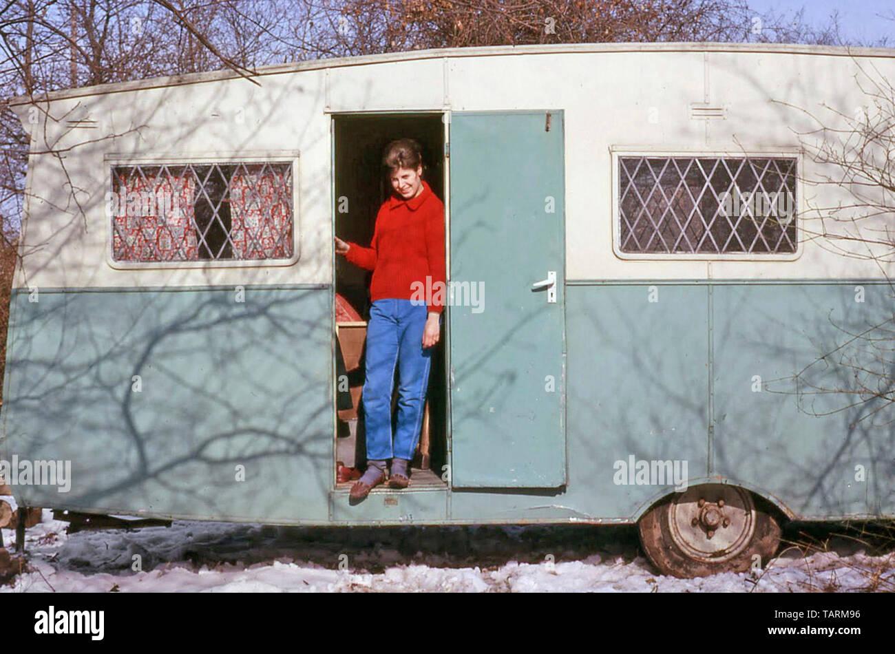 Archivado 1960 recién casada joven de pie en la puerta del ruinoso edificio cubierto de nieve caravana antiguo sitio primero hogar conyugal 60s Inglaterra Imagen De Stock