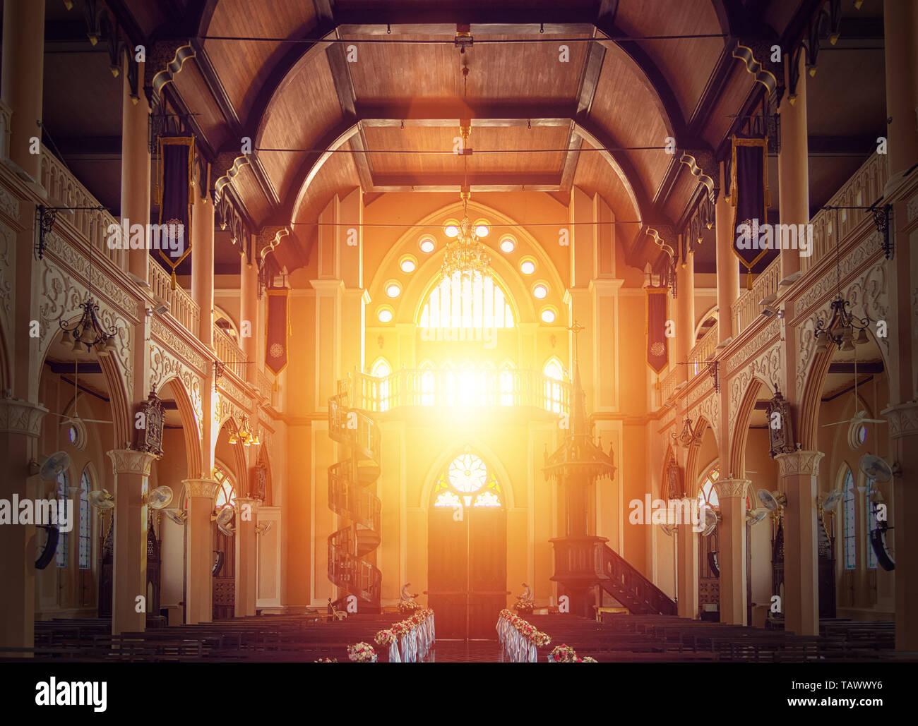 Vista interior de la iglesia vacía con banco de madera decoradas con bouquet de flores, la luz del sol a través de la vidriera de la iglesia Foto de stock