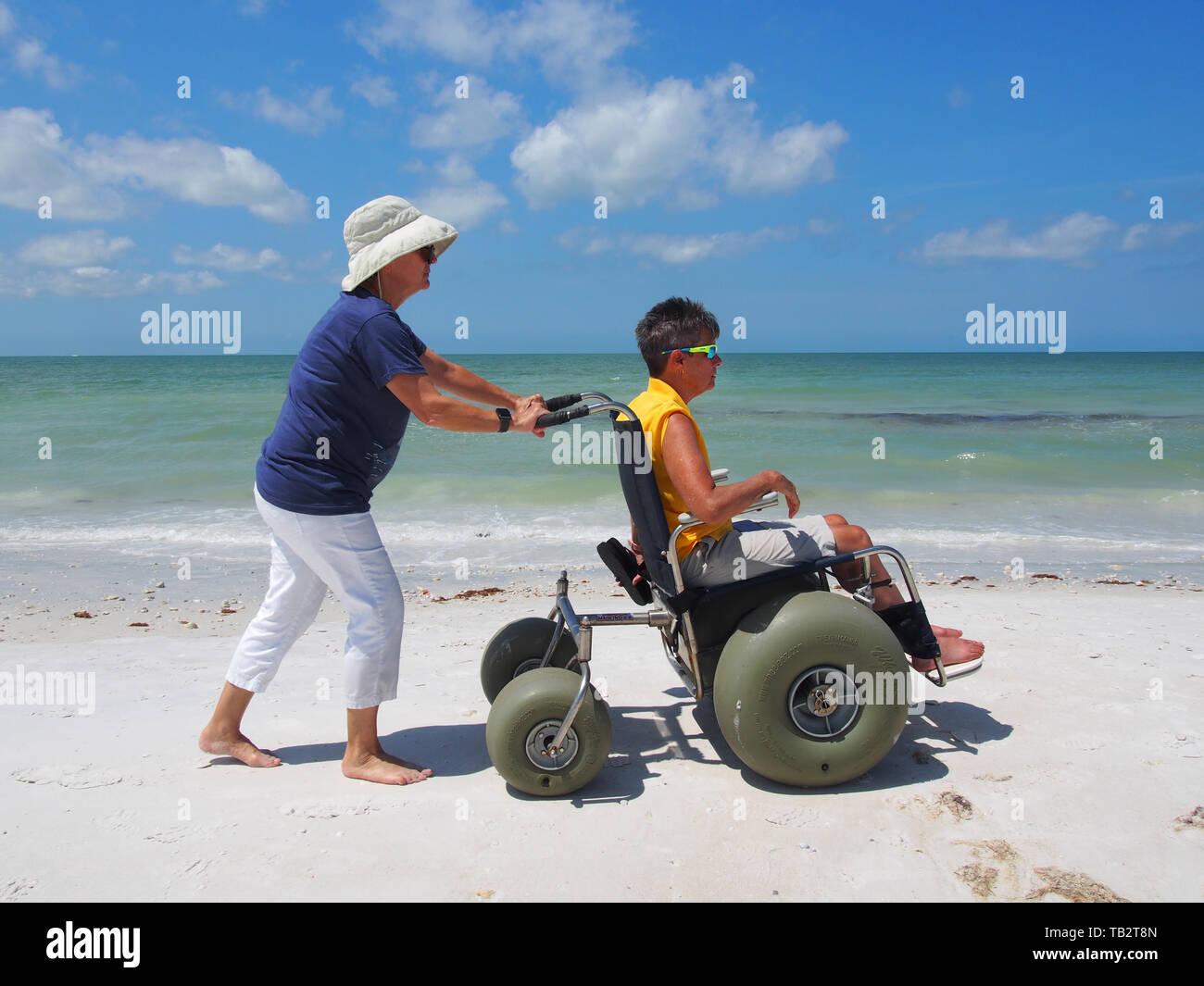 Mujer discapacitada en silla de ruedas de playa goza del sol y la arena en Honeymoon Island State Park, en Dunedin, Florida, EE.UU., 10 de mayo de 2019, © Katharine Andrioti Foto de stock