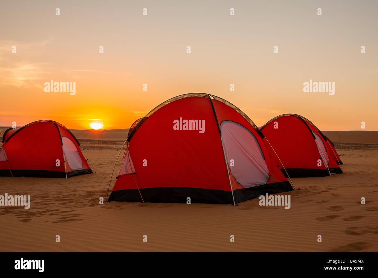 Tres Naranjas hombre dos carpas en el remoto desierto occidental de Sudán lanzó para la noche en la puesta de sol de color amarillo brillante con el sol en el horizonte Foto de stock