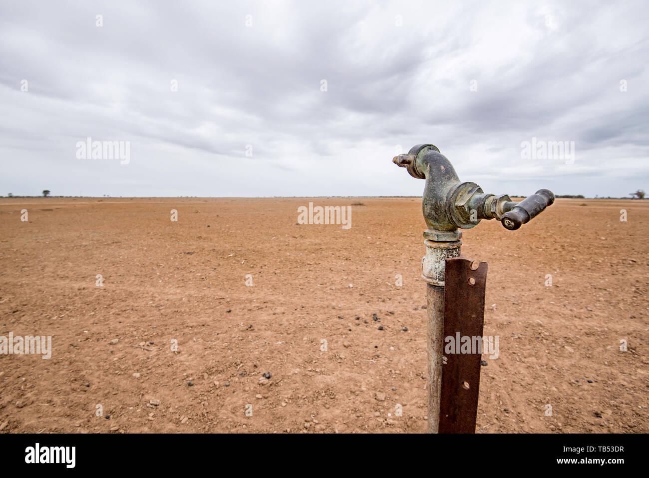 Un solitario tap (grifo) está inutilizable vacía junto a una presa en una sequía afectó a la propiedad en el noroeste de Nueva Gales del Sur, Australia Imagen De Stock