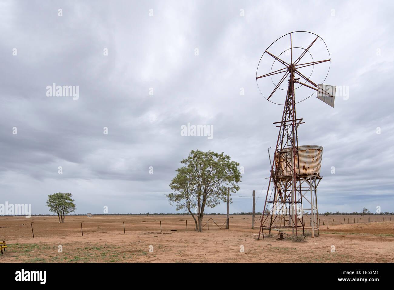 Un viejo e inutilizable el molino de viento y tanque de agua sobre un stand en un lugar seco y la sequía afectó paddock en el noroeste de Nueva Gales del Sur, Australia Imagen De Stock